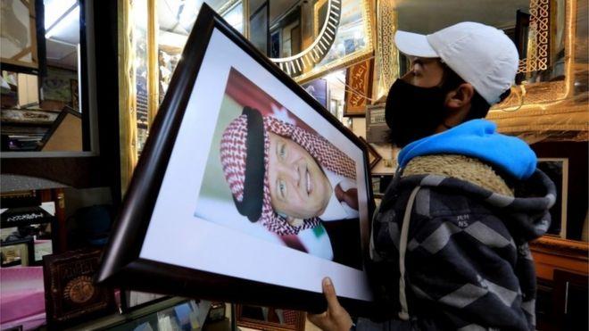 صانع إطارات يعرض صور للملك عبد الله