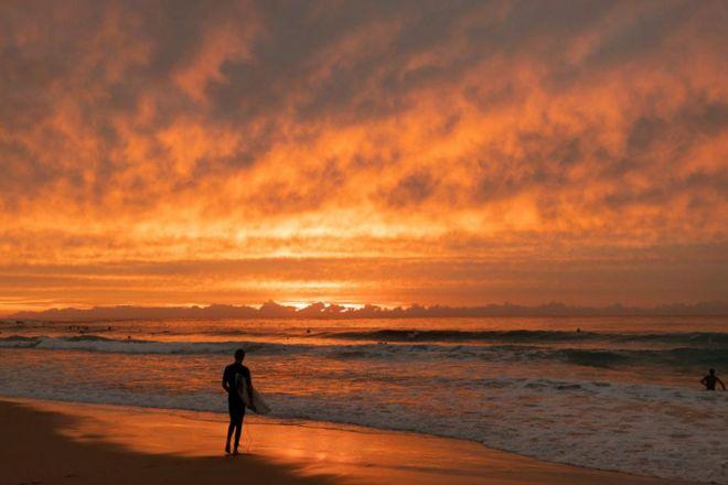 شخص يستعدّ لركوب الأمواج في ماربورا استراليا