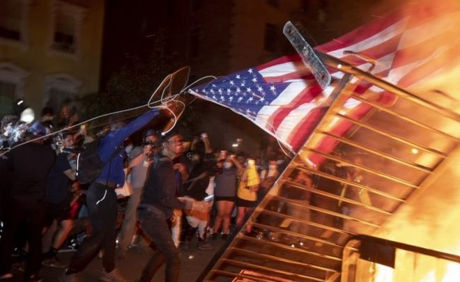 Protesters burn a US flag in Washington DC. Photo: 31 May 2020