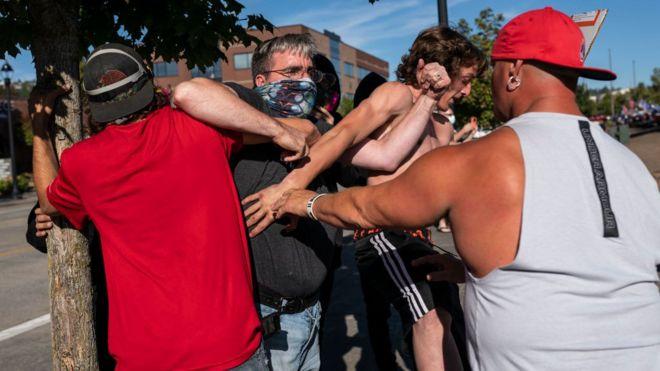 """متظاهر من """"حياة السود مهمة"""" في اشتباك مع أحد مؤيدي ترامب يوم 29 أغسطس 2020"""