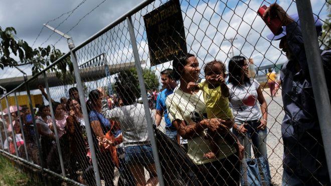 Pessoas formam fila atrás de grade em Paracaraima, na fronteira entre Brasil e Venezuela