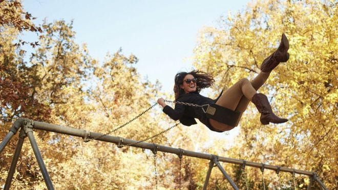 A woman on a swing in autumn