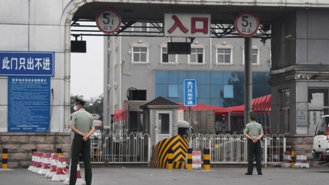 Chinese paramilitary police officers guard an entrance to the closed Xinfadi market in Beijing on June 13, 2020.