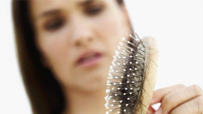 Mulher vê cabelos acumulados em sua escova