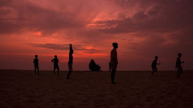 Boys waiting for a corner kick during a game of football on Arthunkal Beach, Kerala, India.