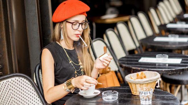 ผู้หญิงกำลังสูบบุหรี่ในร้านกาแฟ