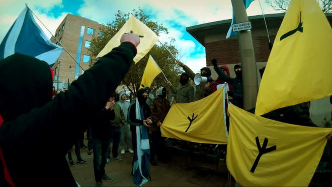 National Action alias group Scottish Dawn demonstrating. some are carrying yellow flags with the Scottish Dawn symbol which strangely resembles a chicken's footprint