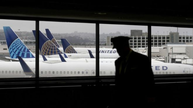 A pilot, in silhouette, walks by United Airlines planes as they sit parked at gates at San Francisco International Airport.