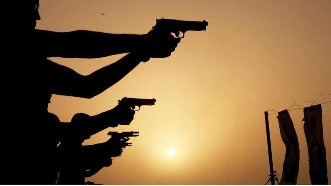 Homens apontam armas
