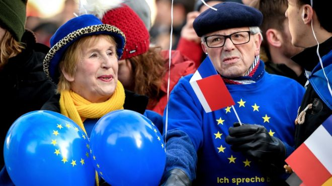 Мужчина и женщина, одетые в яркие синие и желтые цвета ЕС, стоят у барьера, держа на палочке воздушные шары и французский флаг
