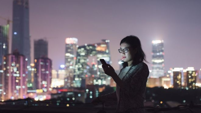 A Chinese woman using her phone