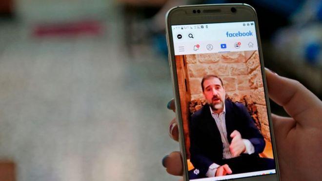 امرأة تشاهد مقطع فيديو لرجل الأعمال رامي مخلوف على فيسبوك