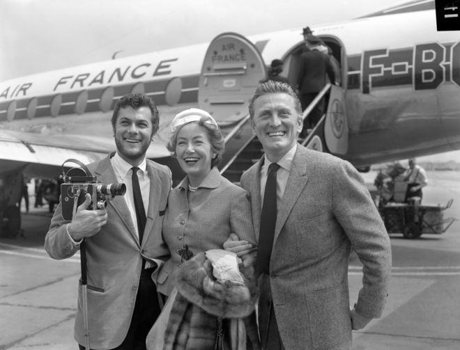 """دوغلاس وزوجته الثانية آن، في لقاء مع الممثل توني كورتس، لدى وصولهم إلى مطار لندن، في 1957، من أجل فيلم """"الفايكينغز"""""""