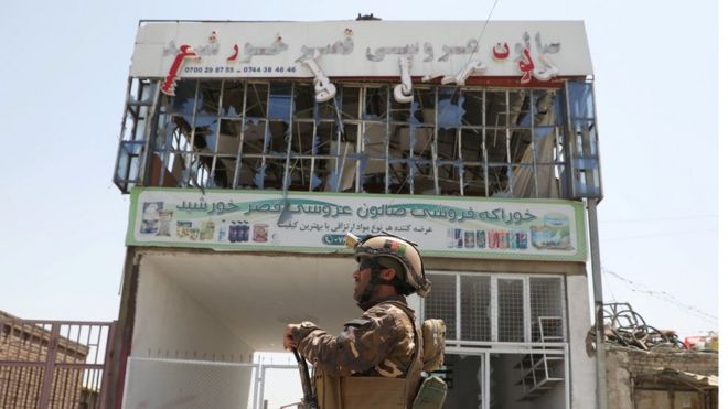 An Afghan soldier patrols in front of a bombed out building in Kabul