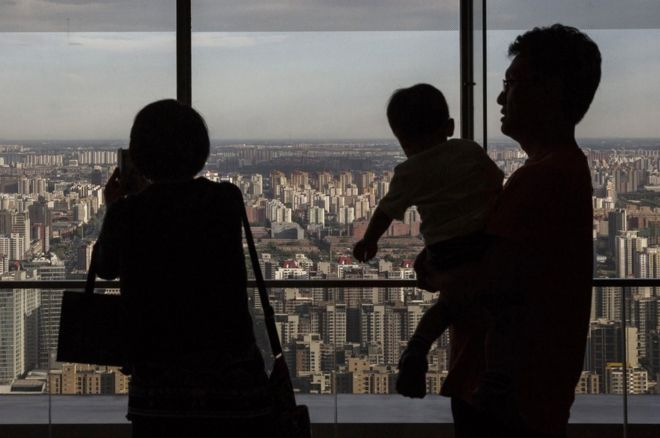 A Chinese couple stand with their child as they look out on residential and office buildings from a luxury hotel on June 11, 2015 in Beijing, China.