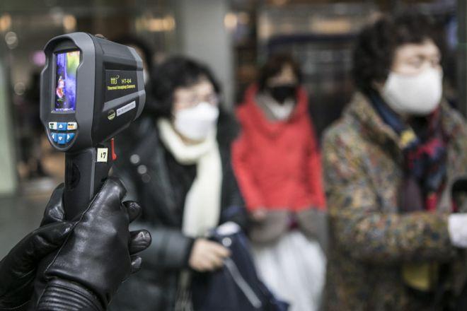 يتم فحص الحاضرين باستخدام موازين الحرارة في حفل زفاف جماعي نظمته كنيسة التوحيد في كوريا الجنوبية.