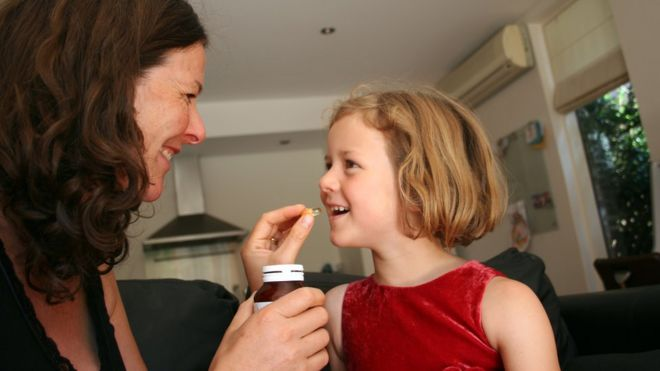 mum giving daughter a vitamin tablet
