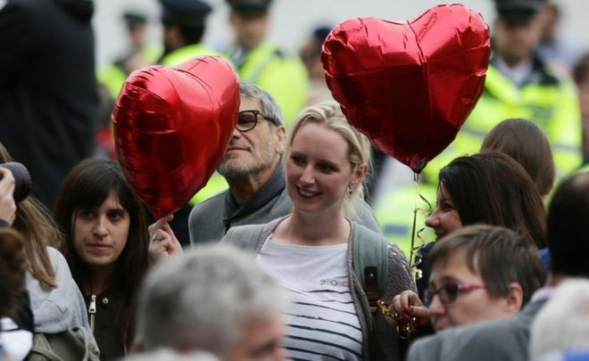A woman holds up two heart-shaped balloons at a vigil in London