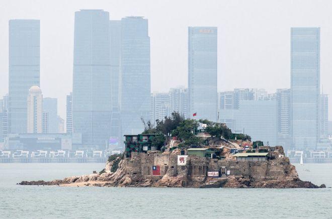 台灣金門離島小島——獅嶼。島上插有中華民國青天白日旗,對面高樓大廈是福建廈門市(2018年4月20日資料照片)。