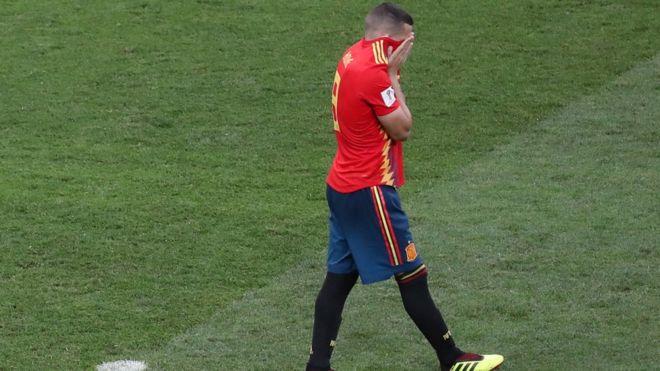 El jugador español Koke se cubre la cara con la camiseta tras fallar un penalti contra Rusia
