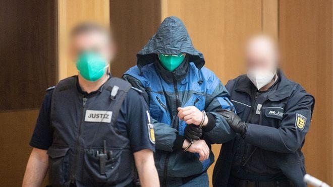 شرطيان يرافقان أحد المتهمين