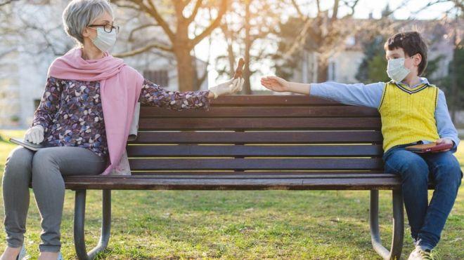 Idosa e criança sentados separados no parque