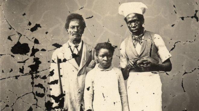Imagem mostra dois adultos e uma criança, ex-escravos, fotografados em estúdio localizado em Porto Alegre, no final do século XIX. Crédito: Acervo do Museu de Porto Alegre Joaquim Felizardo/Irmãos Ferrari