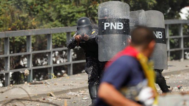 Agente da Polícia Nacional atira balas de borracha contra manifestantes anti-Maduro em Caracas, em 23 de janeiro de 2019