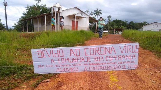 Placa diz: 'devido ao coronavírus a comunidade Boa Esperança não está recebendo visitas de amigos nem de parentes'