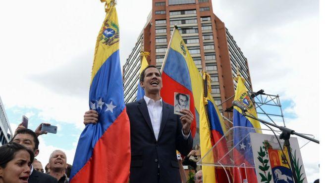 O líder oposicionista Juan Guaidó, que segura bandeira da venezueka, se proclamou o novo presidente interino do país durante protestos de milhares contra o governo de Nicolás Maduro