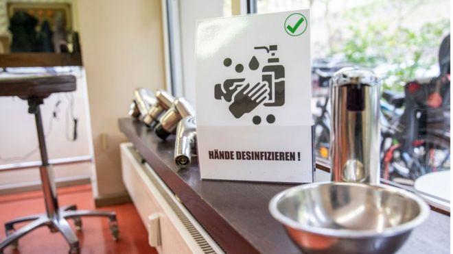 Плакат, напоминающий о необходимости дезинфицировать руки, в парикмахерской в Берлине