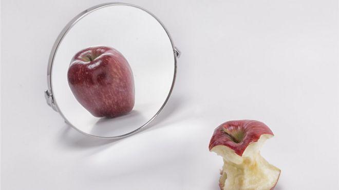 Uma maçã comida em frente a seu reflexo no espelho, onde aparece inteira