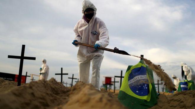 Homem com equipamentos de proteção e uma pá enterrando uma bandeira do Brasil em uma praia do Rio de Janeiro