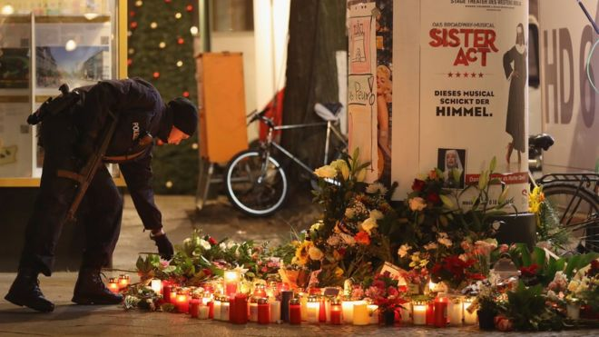 A policeman places a candle on behalf of a mourner at a makeshift memorial the day after a truck drove into a crowded Christmas market in the city center on December 20, 2016 in Berlin, Germany.