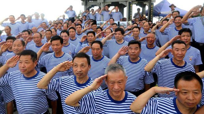 2017年建軍節前,老兵在河南洛陽向國旗敬禮。