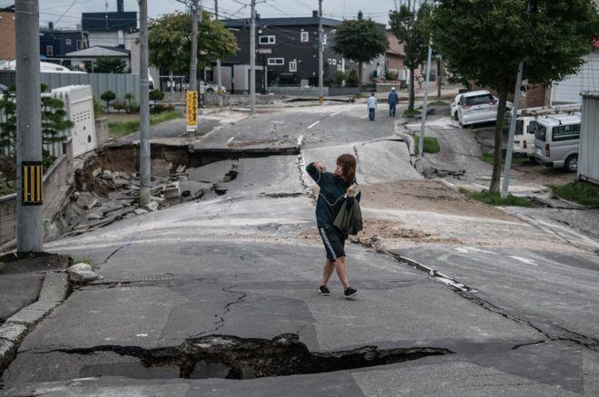 يابانية تسير في طريق دمره زلزال في جزيرة هوكايدو شمالي البلاد