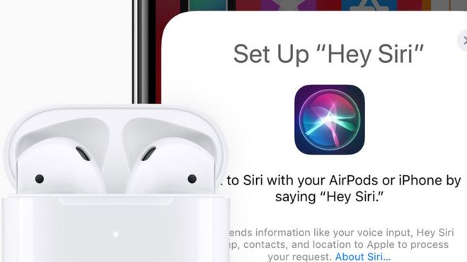 The new AirPods with Siri support shown in front of an iPhone screen