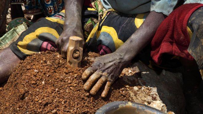 A woman breaks stones containing cassiterite ore at a mine in the Szibira district, Democratic Republic of Congo, in April 2009