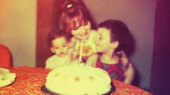 Foto antiga e desfocada com uma mãe e duas crianças em uma festa de aniversário