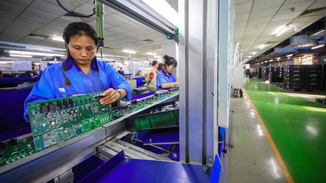 Worker with a circuit board in a Yamaha musical instrument factory in Tianjin