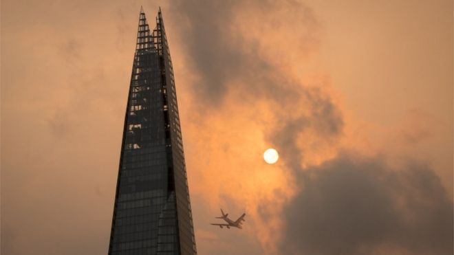 A plane flies past the Shard in central London, as the sky takes on an unusual orange colour