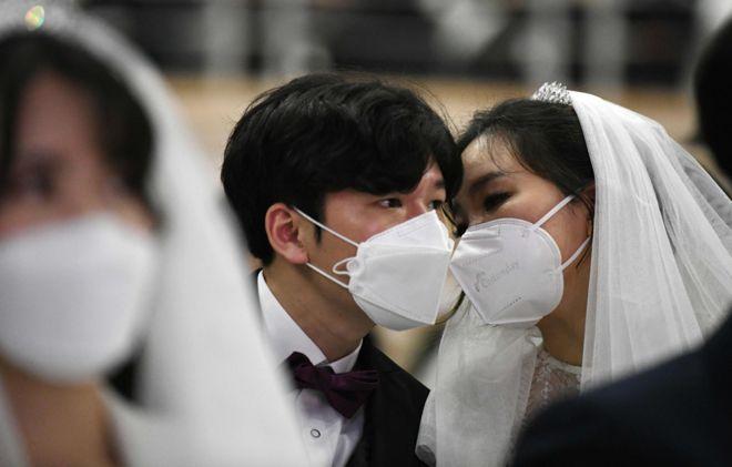 لحظة خاصة بين زوجين يرتديان قناعين خلال حفل زفاف جماعي نظمته كنيسة التوحيد في غابيونغ