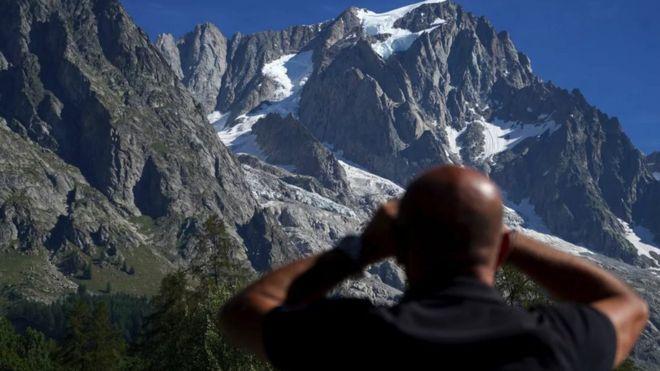 Hombre mirando las montañas en segundo plano.