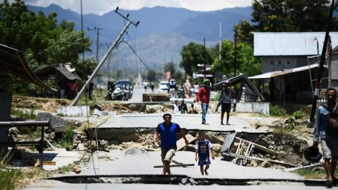 Survivors walk on a damaged street outside Palu in Indonesia's Central Sulawesi on October 2, 2018