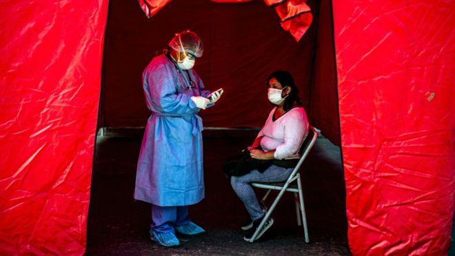 Enfermera tomando una prueba de covid-19 a una mujer