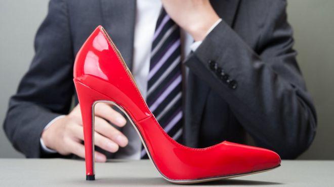 Мужчина смотрит на туфлю на высоком каблуке
