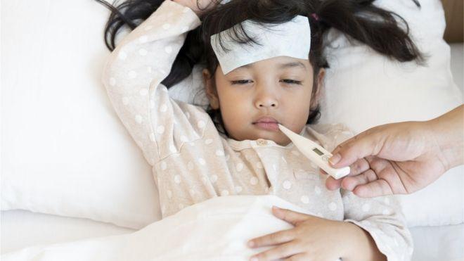 Criança na cama com febre e com termômetro na boca