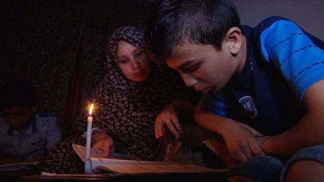 Mother and son read by candlelight in an apartment in Gaza City