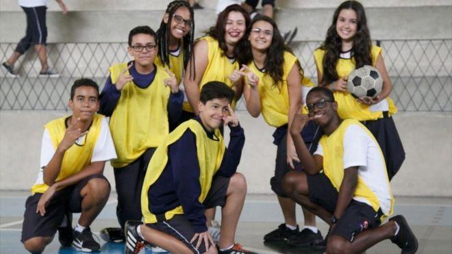 Crianças da escola em babadores esportivos amarelos posam para a câmera, e uma garota detém uma bola