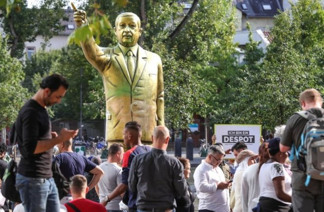 Bystanders look at a gold statue of Turkish President Recep Tayyip Erdogan in the city of Wiesbaden's Square of German Unity